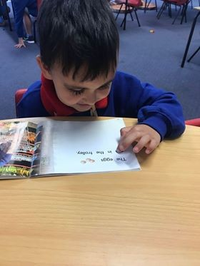 a boy reading the word from the book