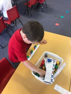 a boy playing coloured beads and legos